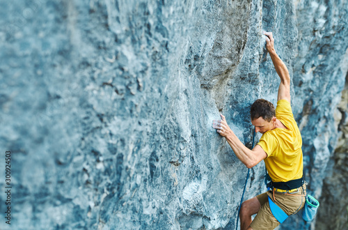top view young strong man rock climber climbing on a high vertical limestone cliff, reaching holds, making hard wide move and gripping hold, attaching rope Canvas Print