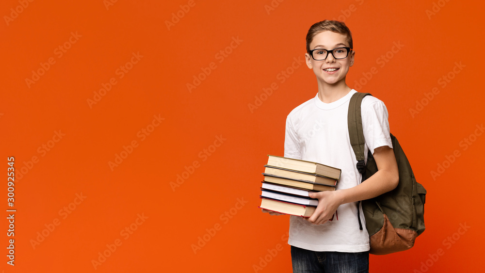 Fototapety, obrazy: Positive teen boy in eyeglasses with backpack holding heap of books