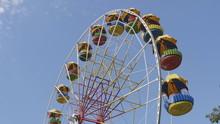 Underside View Of A Ferris Wheel Over Blue Sky.