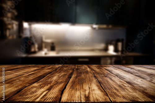 Wooden table background of free space for your decoration and blurred background of kitchen. Copy space.Dark mood interior. Kitchen furniture.