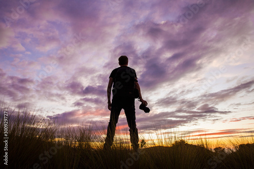 Foto op Aluminium Lavendel Rear view of a young man standing with his photo camera and watching a colourful sunset with purple clouds