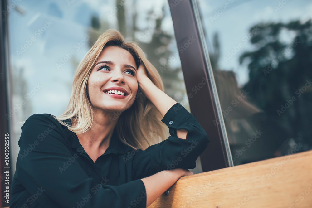Fototapeta Positive cheerful hipster girl with perfect blonde hair taking rest on bench in city and enjoying time for dreaming outdoors, happy female with cute candid smile looking away during leisure