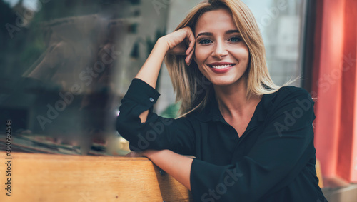 Fotomural  Close up portrait of pretty Caucasian woman with blonde hair taking rest on city