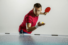 Answer. Young Man Plays Table Tennis On White Studio Background. Model Plays Ping Pong. Concept Of Leisure Activity, Sport, Human Emotions In Gameplay, Healthy Lifestyle, Motion, Action, Movement.