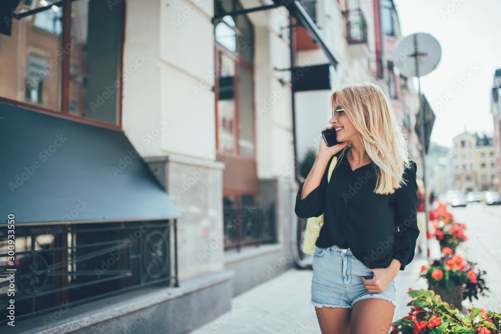 Fototapety, obrazy: Happy successful female tourist enjoying mobile phoning while walking around urban setting and smiling, attractive cheerful hipster girl with blonde hair communicating via smartphone gadget