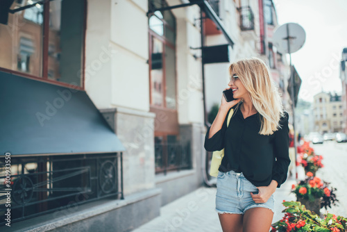 Obraz Happy successful female tourist enjoying mobile phoning while walking around urban setting and smiling, attractive cheerful hipster girl with blonde hair communicating via smartphone gadget - fototapety do salonu