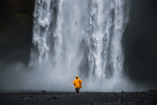 Tourist Wearing A Yellow Raincoat Walks From The Skogafoss Waterfall In Iceland