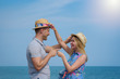 Cute European loving couple in sun hats having fun on the pier near clear blue sea, they smiling, pointing to each other and looking to each other. They are on their honeymoon.