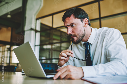 Photo Young bearded agitated entrepreneur checking account balance in online banking service on laptop computer and surprised by numbers