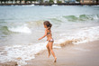 young girl running into the Pacific Ocean