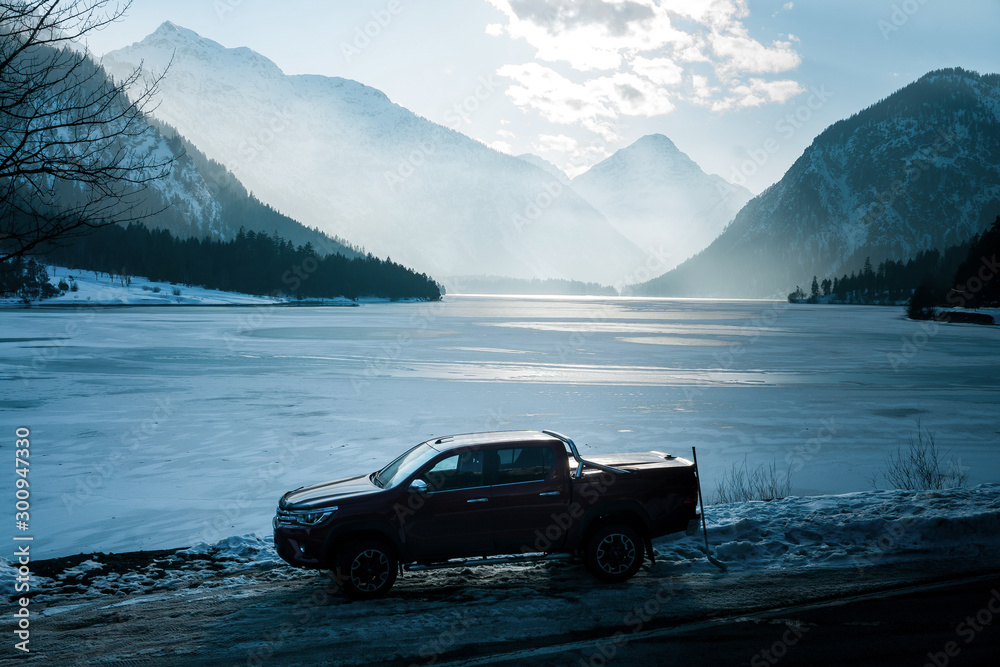 Fototapety, obrazy: Dolomites, Italy -  December, 2018: The red New Toyota Hilux 2018 double cab 4x4 pickup truck running on the mountain road in Dolomite, Italy, winter, snow