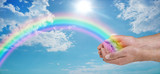 Fototapeta Rainbow - Sending you beautiful rainbow healing energy - male cupped hands with a vivid rainbow arcing outwards against a blue sky, with clouds and a sun burst with copy space
