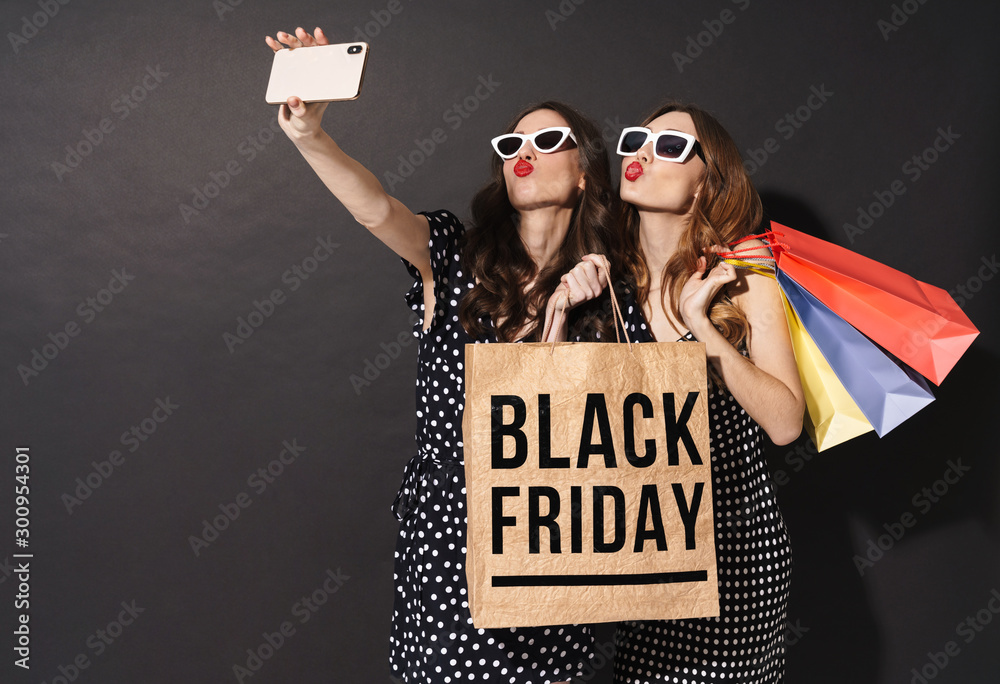 Fototapety, obrazy: Image of girls taking selfie on cellphones and holding black friday bag