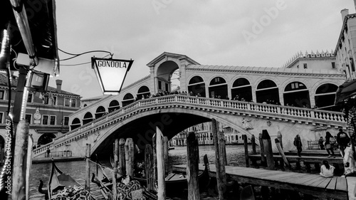 Black and white photo of gondola and gondolier at Rialto Bridge taken in the beautiful city of Venice, Italy