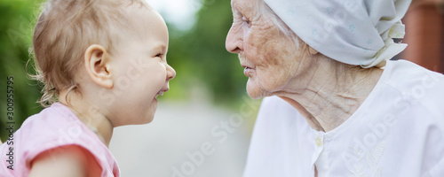 Canvastavla Happy toddler girl and her great grandmother looking at one another, laughing an
