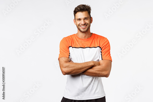 Obraz Handsome smiling man bodybuilder, cross arms over chest, wear sport t-shirt, activewear. Masculine guy talking to team members in locker room, laughing and discussing match, standing confident - fototapety do salonu