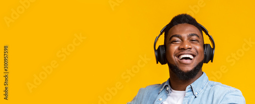 Fotografia  African american man in modern headphones smiling on yellow background