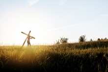 Beautiful Shot Of A Male Carrying A Wooden Cross In A Grassy Field With Sun Shining In Background