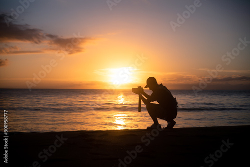 The silhouette of a male hobbyist photographer taking photos of a beautiful colorful sunset on the West Puerto Rico coast near Rincon