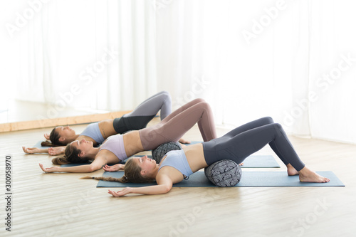 plakat Restorative yoga with a bolster. Group of three young sporty attractive women in yoga studio, lying on bolster cushion, stretching and relaxing during restorative yoga. Healthy active lifestyle.