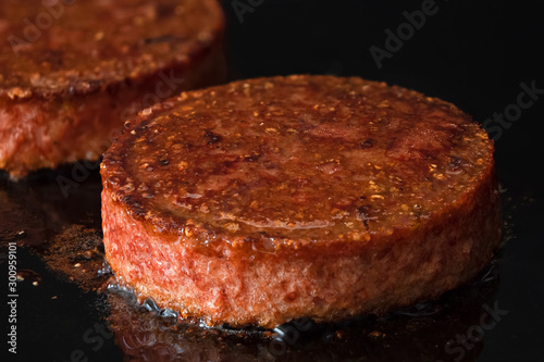 Plant based vegetarian burger patties being cooked on flat black iron grill Canvas Print