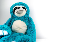 Loveable Sloth Like Blue And White Furred Teddy Bear Sitting On White Table Against A White Background.