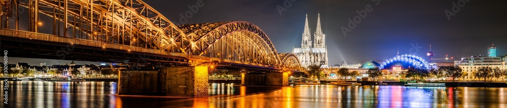 Fototapeta Panorama of the city of Cologne at night with Cologne Cathedral, Hohenzollern Bridge and Rhine river