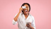 Woman Holding Smartphone And Credit Card Having Fun In Studio