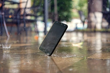 Smartphone Falling And Crashing On Wet Ground In The City Park On A Rainy Day
