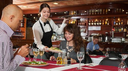 Fototapeta  Young waitress serving couple