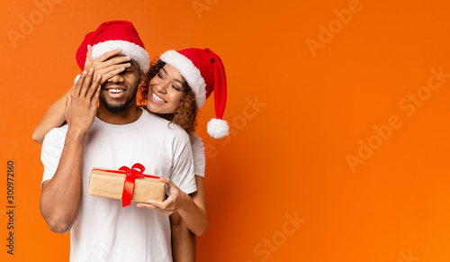 Fotobehang Hoogte schaal Black millennial couple with Christmas gift on orange background