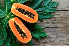 Sliced Half Ripe Papaya Fruit On Wood Background