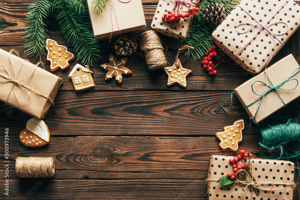 Fototapeta A Christmas background with a copy space for the text. Flat lay with packed gift boxes, gingerbread cookies and fir branches. Cozy holiday mood for postcards.