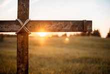 Closeup Shot Of A Wooden Cross With The Sun Shining In The Blurred Background
