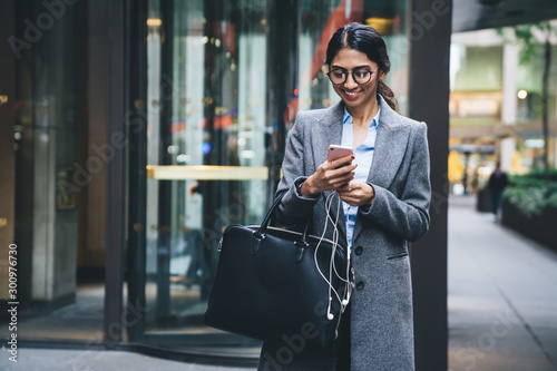 Cheerful young businesswoman texting on cellphone while walking at street