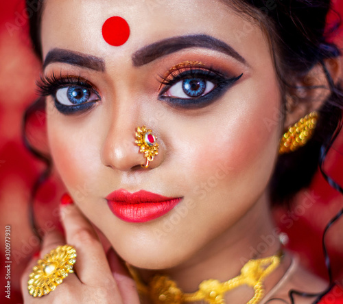 Photo Portrait of stunning Indian bride dressed in Hindu red traditional wedding clothes sari embroidered with gold jewelry and a veil smiles on face