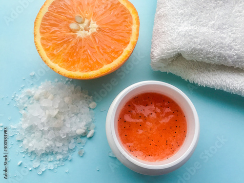 A jar of orange scrub, a white towel, a half of orange and scattered near a large bath salt on a blue background. Spa concept, body cleansing and moisturizing, anti-cellulite