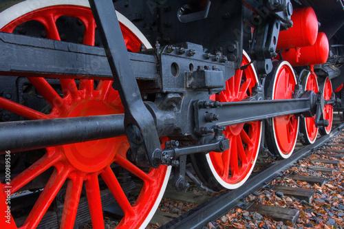 Fotografía  Fragment of a retro locomotive on railway,red wheels of the black locomotive