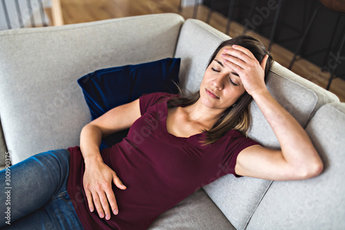 Fototapeta  A Sick woman lying on sofa in the living room with stomach ache