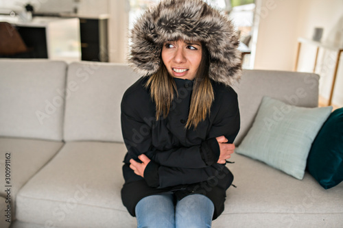 Woman have cold on the sofa at home with winter coat Tablou Canvas