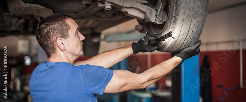 Photo  Auto master mechanic checks condition of the brakes and wheels