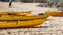 A Row Of Colorful Yellow Kayak...