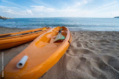 Foto op Canvas Ontspanning Two colorful orange kayaks on a sandy beach ready for paddlers in sunny day. Several orange recreational boats on the sand. Active tourism and water recreation.