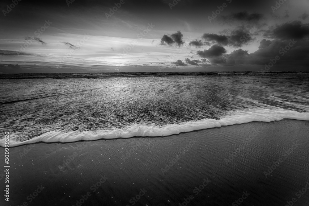 Fototapeta Grayscale shot of a beautiful sunset at the beach creating the perfect scenery for evening walks