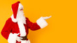Santa Claus holding copy space on palm over orange