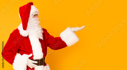 Santa Claus holding copy space on palm over orange Canvas Print