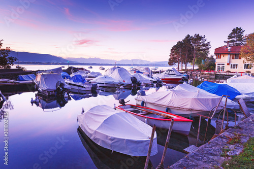 Foto auf Gartenposter Flieder Colorful autumnal scenery of Yacht club at Geneva lake during fascinating sunrise in Switzerland. Beautiful small cozy bay with sheathed recreation boats. Traditional view of lake Geneva. Violet color