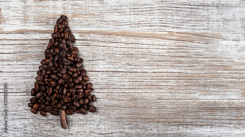 Café en grains Shape of Christmas tree made of coffee beans, anise star and cinnamon sticks, on wooden table. Winter holidays concept. Top view, copy space. Wooden, natural background