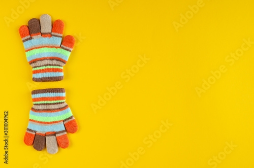Valokuvatapetti Striped kids winted gloves composition on yellow background.