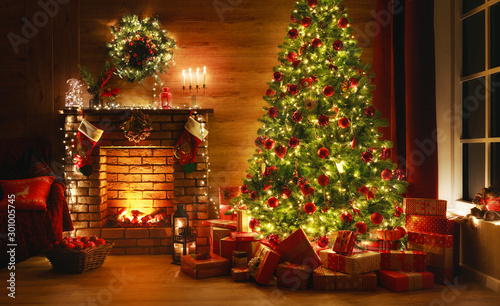 Photo interior christmas. magic glowing tree, fireplace, gifts in  dark